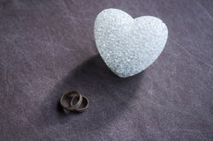 Love, wedding and Valentine`s day concept. Beautiful golden wedding rings and glass heart selective focus. useful as greeting card Royalty Free Stock Photo