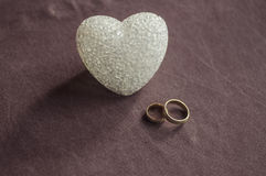 Love, wedding and Valentine`s day concept. Beautiful golden wedding rings and glass heart selective focus. useful as greeting card Royalty Free Stock Photos