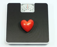 Love weight. A heart is on a weight scale Royalty Free Stock Images