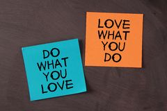 Love What You Do and Do What You Love. 'Love What You Do and Do What You Love' notes pasted on blackboard Stock Image