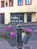 Love what you do. Mainz, Germany – May 15, 2017: Liebe was Du tust love what you do written on a house with flowers in the foreground Stock Photography