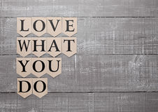 Love what you do motivation symbol on wood board Royalty Free Stock Images
