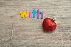 With love where the love is replaced with a red heart bauble. On a wooden background royalty free stock image