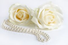 Love in white. Symphony in white, two white roses and a pearl necklace, as a valentine gift Stock Image
