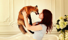 Love of wild animals. Girl with a fox. Stock Image