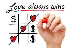 Love Always Wins Over Money Concept. Hand drawing Love Always Wins over money tic tac toe concept with marker on transparent glass board isolated on white royalty free stock photo