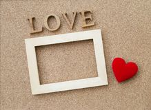 Love wooden text and wooden frame with red heart. On corkboard texture Stock Images