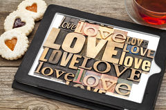 Love word abstract typography. Love word abstract - in vintage letterpress wood type printing blocks on a digital tablet with cup of tea and heart cookies royalty free stock images