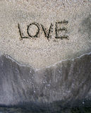 Love word in the beach. Love word written in beach with sea waves Royalty Free Stock Image
