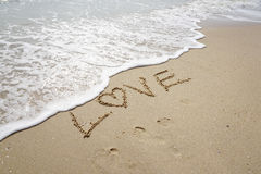 Love word on on the beach. With sea wave Stock Image