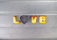 Love word, biscuit cookies letters with heart shaped cookie cutte Stock Photos