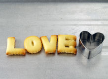 Love word, biscuit cookies letters with heart shaped cookie cutter Royalty Free Stock Image