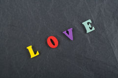 LOVE word on black board background composed from colorful abc alphabet block wooden letters, copy space for ad text. Word on black board background composed royalty free stock photography