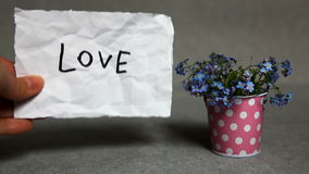 Love - word with blue flowers on gray background stock footage