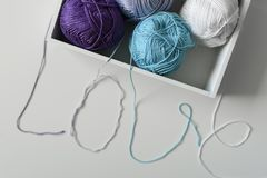 Love word designed from cotton threads from yarn balls in white box. Idea for love word designed from cotton threads from yarn balls in white box stock photos