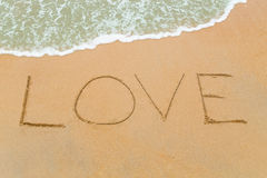 LOVE word drawn on sandy beach with wave approaching Royalty Free Stock Image
