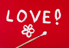 Love word with flower painted over red Royalty Free Stock Photo