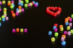 Love word folded with colorful cubes with letters and a heart on a black background.  stock photography