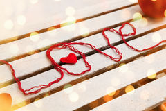 Love word formed with red knitting yarn on wooden background Royalty Free Stock Images