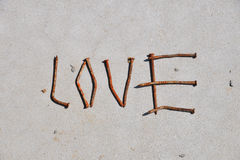 LOVE word formed by rusty nails at grey concrete background Stock Photos