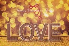 Love word on gold bokeh retro background Stock Photos