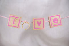 Love word from gold ring and small wood cube hanging on the rope Stock Photos