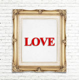 Love word in golden vintage photo frame on white brick wall,Love concept Stock Photography