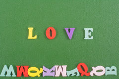 LOVE word on green background composed from colorful abc alphabet block wooden letters, copy space for ad text. Learning. Word on green background composed from Stock Images