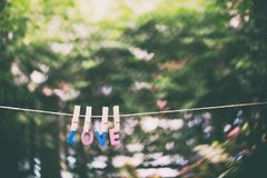 Love word hanging by rope with beautiful colorful heart bokeh n. Ature background vintage retro tone, Valentines and wedding day greeting card background concept stock photo