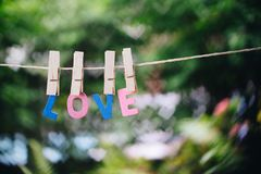 Love word hanging by rope with beautiful colorful heart bokeh n. Ature background, Valentines and wedding day greeting card background concept stock photo