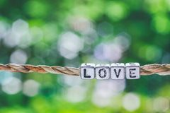 Love word hanging by rope with beautiful green nature bokeh back stock photos