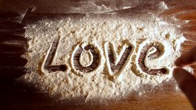 Love word and the heart on flour. Erase inscription stock footage