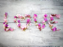 Love word made of flowers on wood background for valentine day Stock Photo