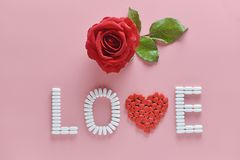 LOVE word made from medicine pills and red rose on pink background. Concept of Valentine`s Day stock photos