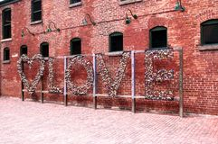 Love word made out of locks. The word love made out of locks, old brick background, Distillery District, Toronto, Canada stock image