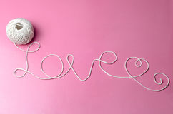 LOVE WORD MADE OF WHITE THREAD. Image of a white thread forming love words with pink background stock photo