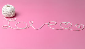 LOVE WORD MADE OF WHITE THREAD. Image of a white thread forming love words with pink background Stock Image