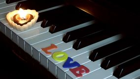 Love Word on piano key. And Candles stock video footage