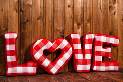 Love word of plush red letters on wood background Royalty Free Stock Photo