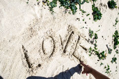 Love word in the sand. Love word written in the sand at the beach Stock Images