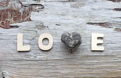 Love. Word with stone heart on wooden vintage scratched background stock images