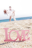 Love word on tropical background, beach wedding concept. Love word on natural tropical background, beach wedding concept, loving couple in the background Royalty Free Stock Photography