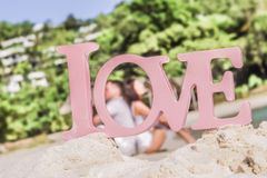 Love word on tropical background, beach wedding concept Stock Images