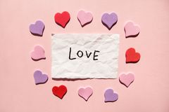 Love - word on white paper with hearts on pink background, valentines day royalty free stock photography