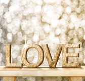 LOVE word in wood texture on wooden table with gold bokeh backgr Stock Images