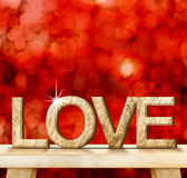 LOVE word in wood texture on wooden table with red bokeh backgro Stock Photo