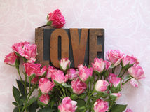 Love word in wood type with roses Stock Photos
