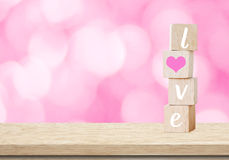 Love word on wooden cubes over blur bokeh background, valentine concept Stock Photo