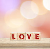 Love word on wooden cubes over blur bokeh background , valentine Royalty Free Stock Photography