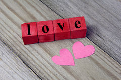 Love word on wooden cubes and two paper heart on wooden background Royalty Free Stock Photos